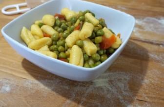 Malloreddus fatti in casa con talli d'aglio e piselli freschi con un tocco di zenzero
