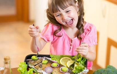 Funny child girl and grilled fish at kitchen. Healthy eating seafood.