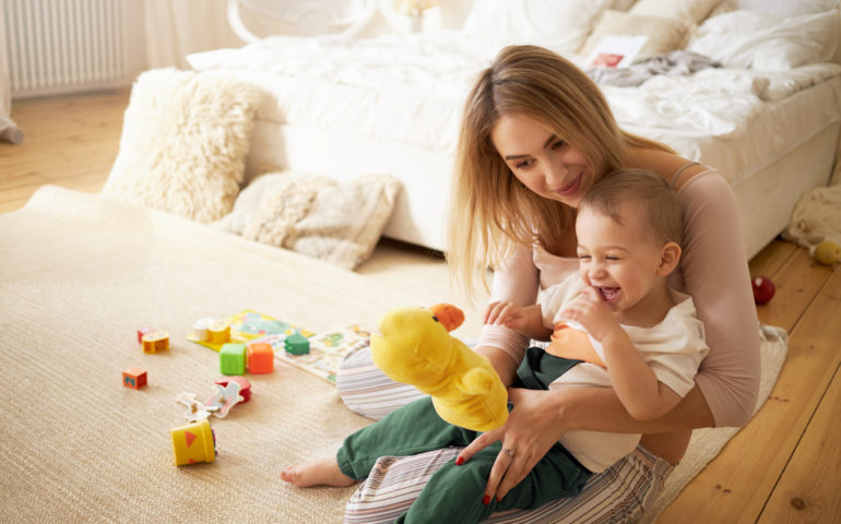 Pretty sister spending time with her baby brother, sitting on floor in bedroom. Beautiful young babysitter playing with little boy indoors, holding stuffed toy duck. Infancy, childcare and motherhood