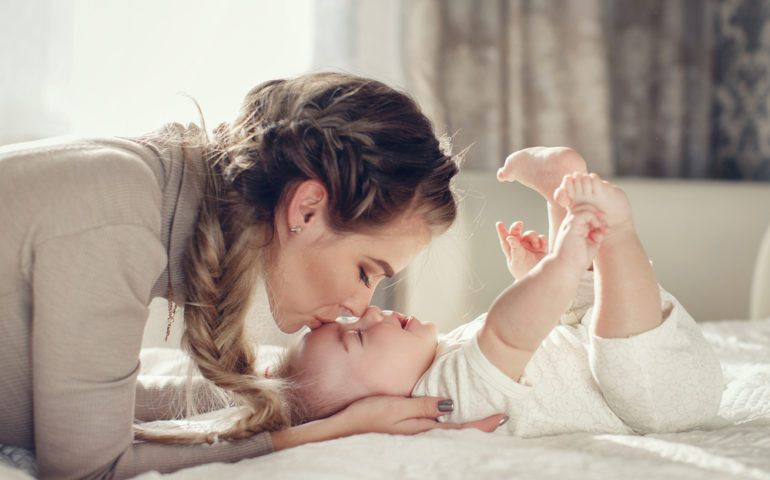 Young,Mother,Holding,Her,Newborn,Child.,Mom,Nursing,Baby.,Woman